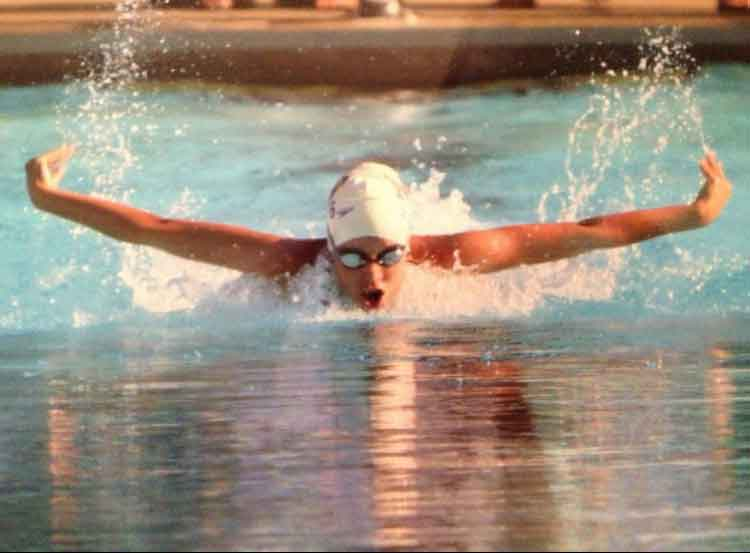 Leaping out of the water, junior Hannah Palmeter swims the 100-meter butterfly at the 2013 sectionals.