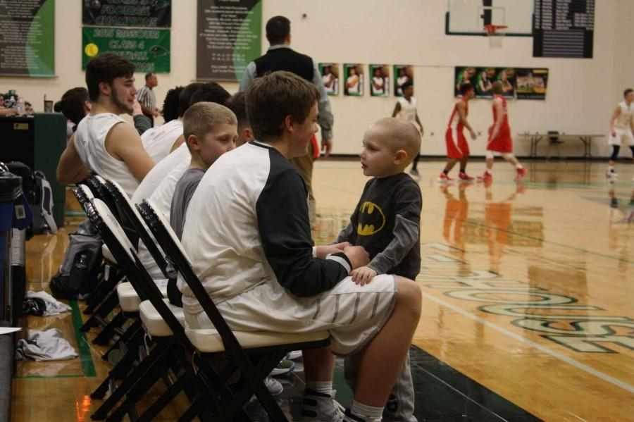 """Cancer Patient Rhylan Lopata, 5, who is currently undergoing chemo therapy, sat the bench with the Varsity Basketball Team on February 2 in which they won against Fort Osage 71-52 at the Falcon Fieldhouse.  The team named him and his brother honorary coach for the night. """"It made me feel good to help someone so young going through something so hard,"""" said sophomore varsity player Bennett Holloway, """"It was really inspiring to watch him go through something like cancer and help him through that."""""""