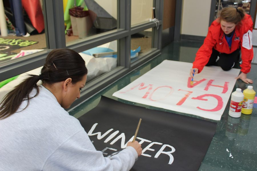 """In preparation for winter informal, juniors Kylee Sally and Britlyn Sparks painted posters. The purpose of the poster was to inform the student body of the dress code. """"I was assigned to be on Tim's committee which meant we were in charge of poster making and spirit days,"""" said Sally."""