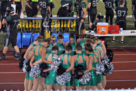 "The Emeralds are praying before performing at the home football game against North Kansas City on Aug. 25. Each person in the group puts a foot in the middle to clear their minds and pray. ""It's our make it or break it moment. It's the moment where we unite as a team so we can execute our dance successfully on the field,"" said sophomore Grace Siegfried."