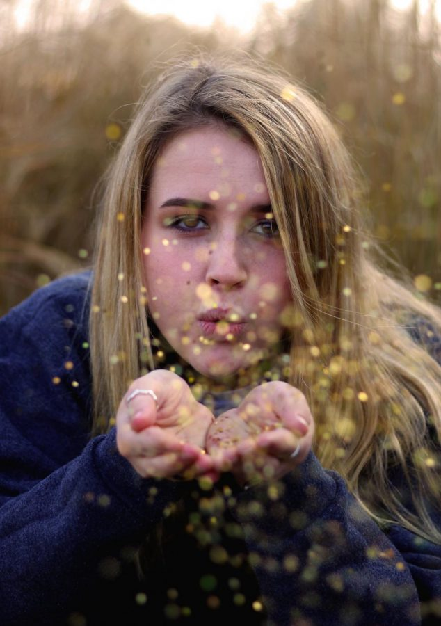 For+Emilie+Kerr%27s+AP+Art+Portfolio%2C+her+concentration+is+portraits+with+some+sort+of+motion.+In+this+photo%2C+senior+Evelyn+Shelby+is+blowing+glitter+in+order+to+help+meet+the+requirements+of+her+idea.