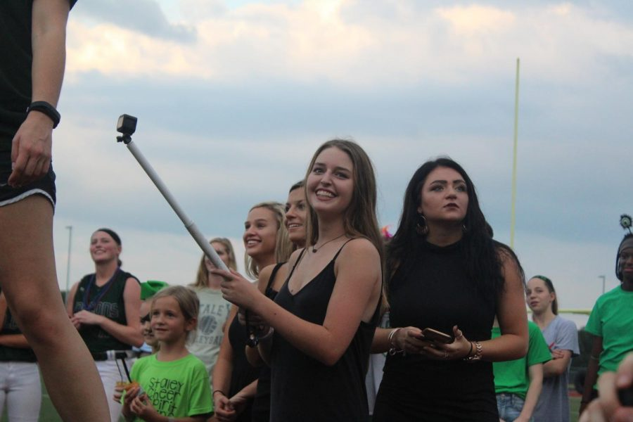 """Filming for her next hype video at the pep rally on Sept. 20, junior Pierson Beaulieu records the students yelling a chant.  She  normally recorded the student section, cheerleaders, Emeralds and players during games. """"I hope to make more videos for other sports,"""" said Beaulieu."""
