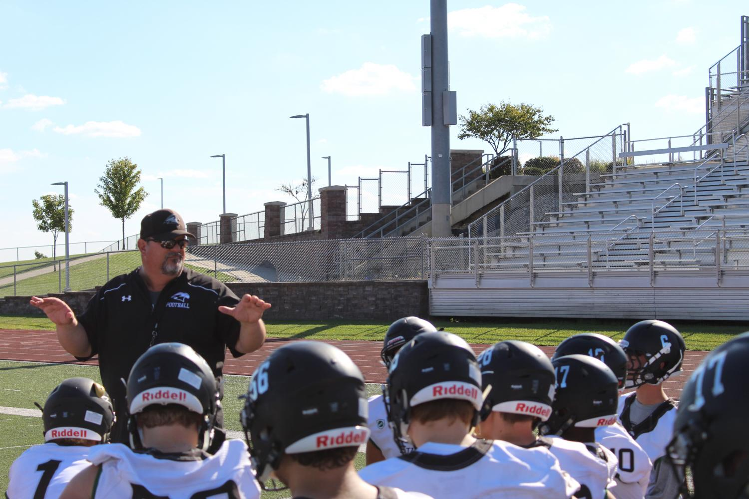 """On Sept. 28, head coach Phil Lite gives the team a post-practice talk. It was the day before a game, and the players had just gotten done with walk throughs. """"He's a good speaker, and he just gets us ready to play. He's a coach on the field but like a friend off the field,"""" said varsity quarterback senior John Raybourn. Photo by Leidy Venegas"""
