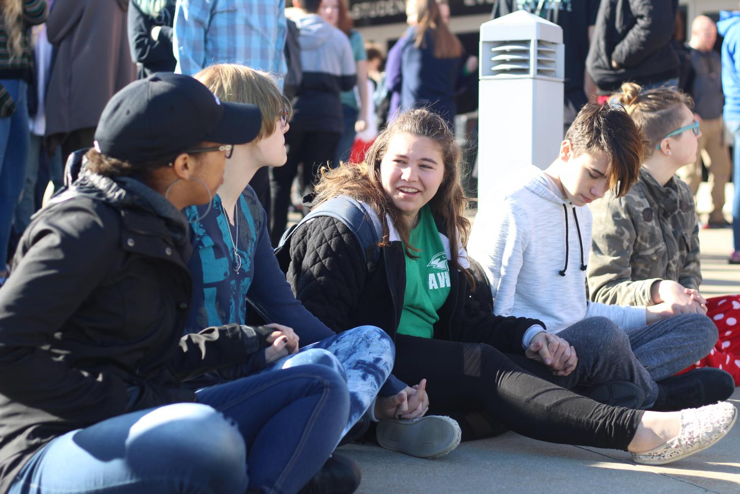 "While participating in the walkout on March 14, sophomores Lexi Valdez, Naomi Davis, Maria Engemann, Tanner Sneed and Shayla Crumb-Potmesil sit and hold hands out of respect for the 17 victims of the Parkland, Fla., school shooting. #NationalWalkoutDay was trending globally on Twitter to cover all the walkouts  across the country. ""We wanted to sit down to make it better because everyone else was standing and talking and laughing, instead of paying attention to the ones who passed away,"