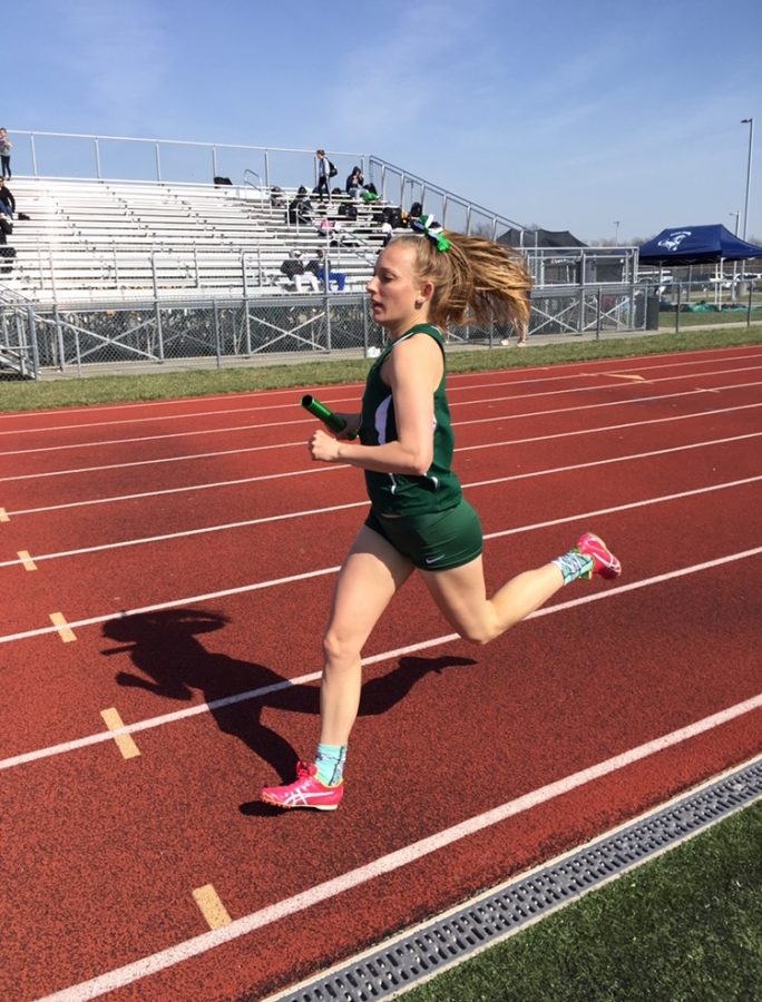 Running+the+4x8%2C+sophomore+Alex+Hamre+gets+ready+to+hand+the+baton+off+as+she+runs+her+last+lap+where+on+March+20.+Hamre+trained+hard+and+ran+in+every+varsity+meet+in+order+to+reach+her+goal+of+breaking+the+3200-meter+record.+%E2%80%9CI+would+do+around+two+hard+workouts+a+week+to+help+me+train+for+it%2C+and+I+had+coach+Adair+help+me+by+yelling+out+my+splits+each+400+to+tell+me+whether+I+was+on+pace+or+not%2C%E2%80%9D+said+Hamre.+