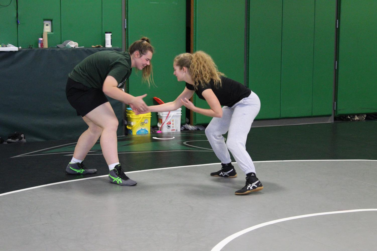 """Sophomore Madison Schmude and Remi Asta, sophomore, partner up before practice to start warming up on November 8th. They start by hand wrestling and working other wrestling moves on the mat. The season started on October 29th. """"What happens in the wrestling stays in the wrestling room,"""" says Schmude."""