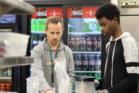 "At the concession stand, junior Hashim Abu prepares smoothies with ELL teacher Travis Mauzey Nov.16. Abu manages the money raised and paperwork for the smoothie production. ""It"