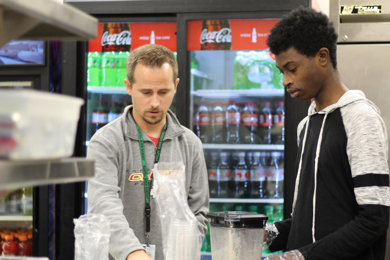 At the concession stand, junior Hashim Abu prepares smoothies with ELL teacher Travis Mauzey Nov.16. Abu manages the money raised and paperwork for the smoothie production.