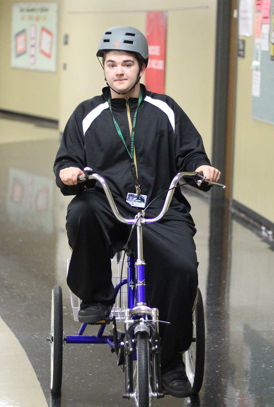 "In the hallway on May 2, senior Josh Roush rides the new tricycle. It was not the senior's first time on a tricycle. ""[Roush] just nailed it,"" said to Rohlfing."
