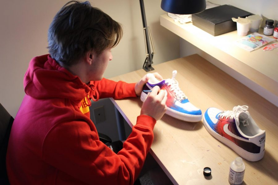 "At his desk, junior Keagan Kooi puts the finishing touches on a new pair of shoes. ""It's something I enjoy doing. I think it's cool to put your own personal touch on a pair of shoes,"" said Kooi."