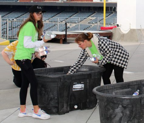 """For participants of the ALS walk, junior Kate Hanchette and NHS club sponsor Carol Toney distribute water bottles among bins. Toney decided to participate in the walk because she wanted to help a cause that connects to her personally. """"My brother-in-law was diagnosed with ALS in 2013, so he has been battling ALS for the past eight and a half years. ALS is central to our family because my husband is also a caregiver for him,"""" Toney said."""
