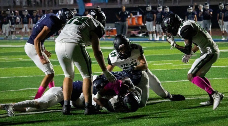 Sophomore Ken'Veon Stone lays on the ground as sophomore Tyler Kerkhoff (#79), senior Anderson Hendershot (#27) and senior Emonta Hicks (#10) rush over to celebrate.